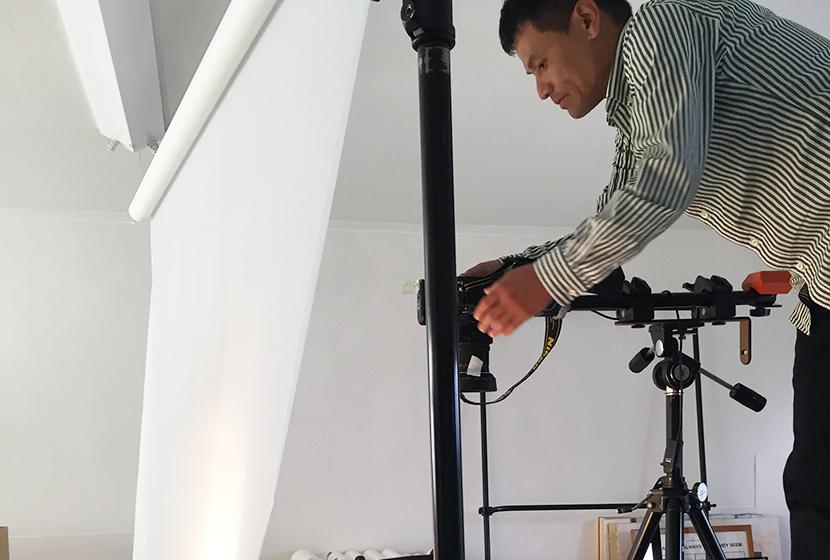 伊と幸の絹の白生地を撮影中の福尾カメラマン