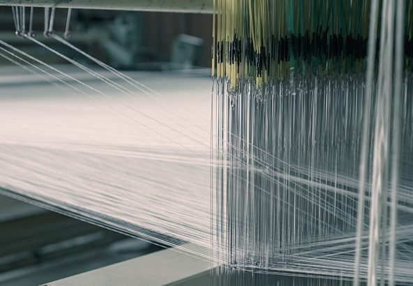 丹後産地の職工部で織りの経て糸を継ぐ